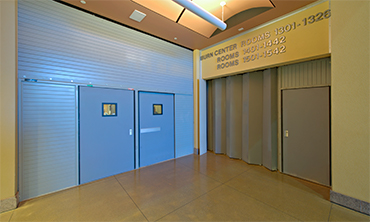 Side Acting Fire Rated Accordion Fire Door Providing Elevator Separation within an I-2 Occupancy